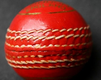 Bright red mini cricket ball