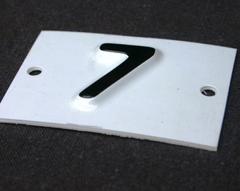 Magical Seven. Vintage black and white embossed plastic house number.