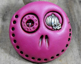 Fuchsia round skull with a tiny pumpkin in his eye. Brooch, keychain, pendant or magnet (you choose)