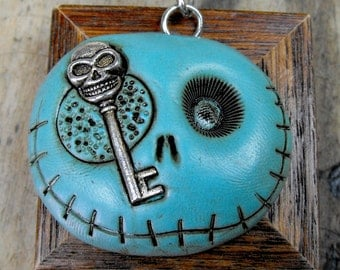 Sky blue round skull with a creepy metal key in his putrefied eye. Brooch, keychain, pendant or magnet (you choose)