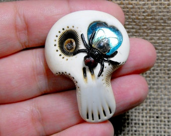 White sugar skull with a blue shiny heart inside his eye and a black fly on the face. Brooch, keychain, pendant or magnet (you choose)