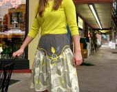 Women's knee length skirt Slimming asymmetrical yoke embellished with yellow and grey braid, leaves, and flowers.