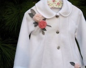 White swing coat for toddlers embellished with pink roses and grey leaves and black and white gingham ribbon..