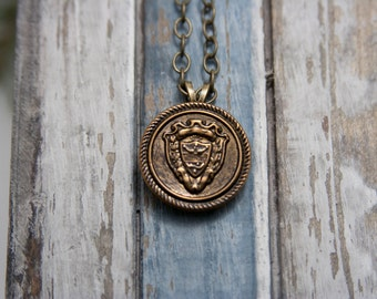 Coat of arms/Family Crest Pendant Necklace with a brass colored chain.