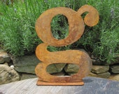 "Lowercase metal letter ""g"" on stand"