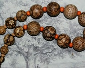 Pyrographed wooden necklace, each bead uniquely decorated.