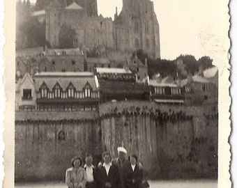 Group posing in front of a fortified castle, vintage photograph