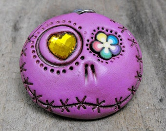 Fuchsia round skull with asymmetrical eyes: a shiny yellow heart and a rainbow flower. Brooch, keychain, pendant or magnet (you choose)
