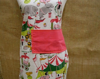 CIRCUS DAY children's apron with fun circus themed print. Pink accent pocket and ties