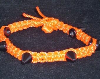 Bracelet, spiked macrame, orange with black spikes