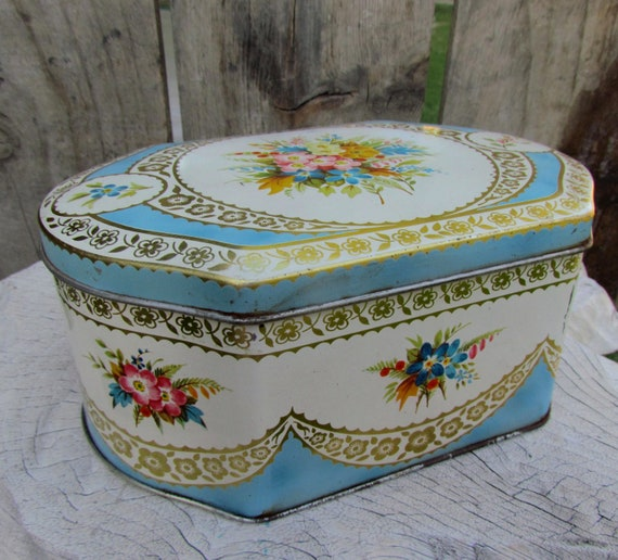 Vintage biscuit tin in baby blue and roses trunk style.