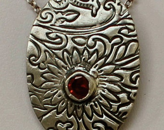 Handcrafted Fine Silver Oval Flower Patterned Pendant with a Garnet Red CZ