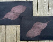 Two black cotton placemats with a stenciled dotted grid