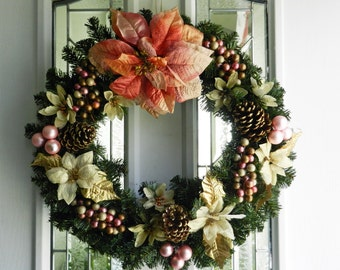 Pink and gold Poinsettia christmas wreath with pine cones, berries and christmas balls  .