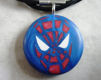 Spider Hero hand carved on a polymer clay blue pearl color background. Pendant comes with a 3mm necklace.