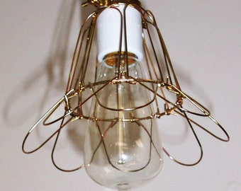Hanging light fixture with industrial cage in brass finish and antique Edison style light bulb - ready to hang