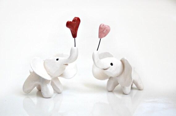 Miniature elephant holding pink heart heart