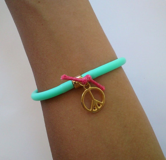 Neon Turquoise rubber bracelet with gold planted peace charm