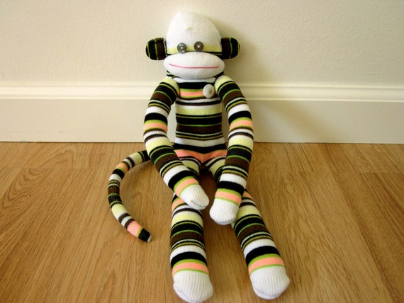Striped sock monkey plush doll - brown, white, yellow, peach, and black, with vintage button