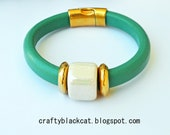Leather bracelet in ultramarine green / sea turqoise colour with white ceramic bead, metallic parts and magnetic clasp.