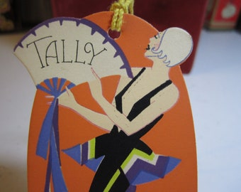 1930's art deco die cut oval shaped bridge tally card deco lady wearing elaborate jumpsuit with neckline to the navel holding a fan gibson