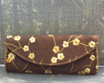Brown clutch with embroidered gold flowers.