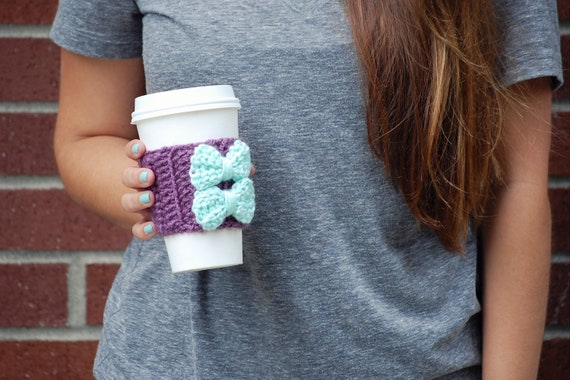 crochet coffee cozy sleeve in purple with two mint bows.
