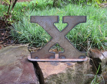 """Lowercase metal letter """"x"""" on stand"""