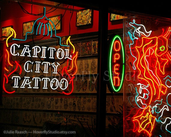 Neon signs in a shop window at night capitol city tattoo for Neon tattoo signs