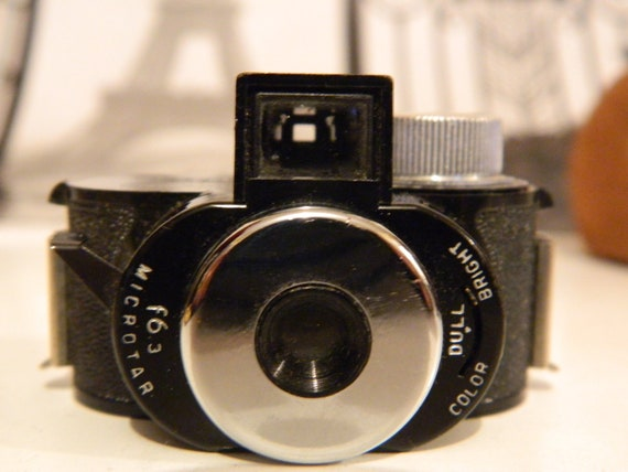 """Miniture """"Pixie"""" Camera with Pixie instruction book and handy dandy swede carry case."""