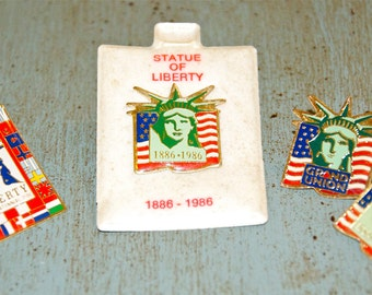 Four vintage 1980s Statue of Liberty pins...