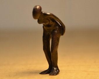 Bronze sculpture of bending female figure