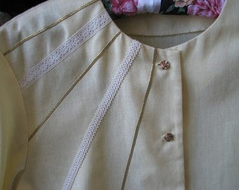 Pale yellow, linen blend, short sleeved, round necked blouse with decorative braid
