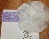 White bling flower on a purple crochet headband