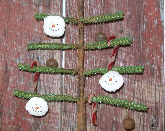 Primitive Faux Feather Tree with Primitive Snowman faces, candy canes and jingle bells ornies