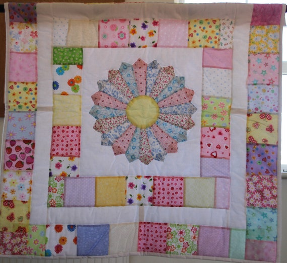 Hand made patchwork quilt with a large daisy in the centre, playmat or crib sized  pastel colours.