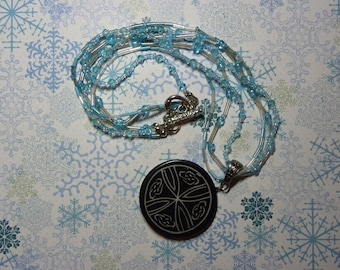 Necklace: Blue, Silver, and White Beaded Necklace with Black and Gray/White Round Pendant