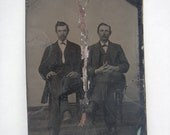 Antique tintype photograph of two men sitting cross legged wearing a three piece suit.