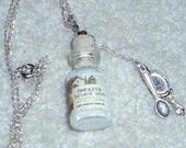 """Little glass bottle of """"cocaine tooth drops"""" with silver spoon and mirror charms"""