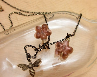 Bees in the Flowers. Brass bee charm with glass flowers on black two-tone chain