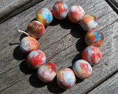 A strand of 12 multi color ceramic round beads