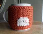 knitted mug cozy cup cozy in burnt pumpkin orange with felt tea patch