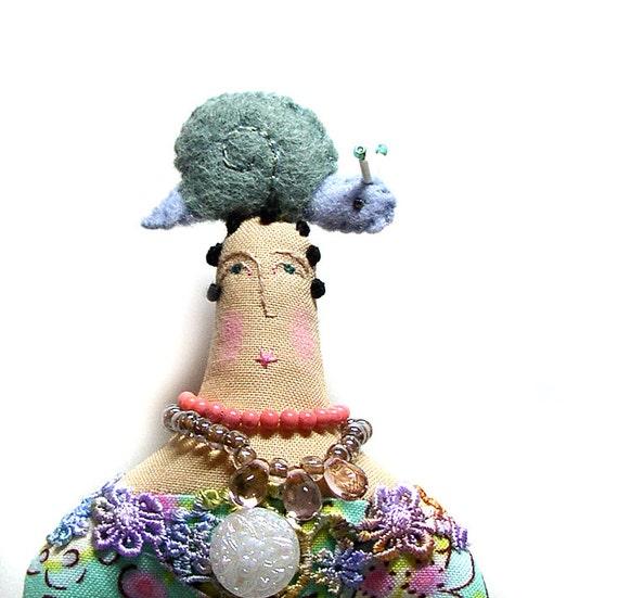 Cloth art doll with felt snail on top of her head