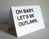 oh baby, let's be outlaws greeting card - black