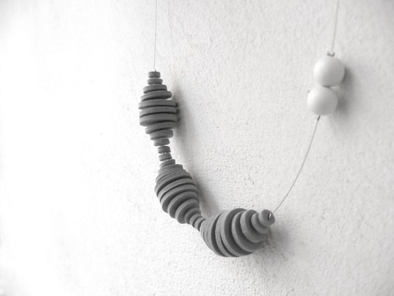 grey minimal geometric necklace with circles and two white dots