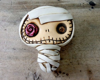 Adorable baby mummy bandaged in white with a hot pink rose in his eye. Brooch, keychain or pendant (you choose)