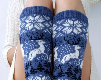 Knit leg warmers with deer, snowflakes, stars ornament made of wool in blue, white and black