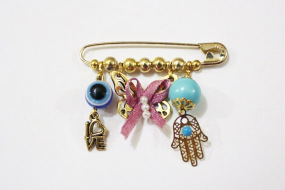 Baby charm collection on safety pin with evil eye and Hamsa charm