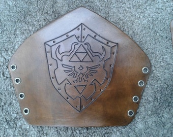 Antique brown leather bracer with hand carved Zelda Hylian shield . Legend of Zelda