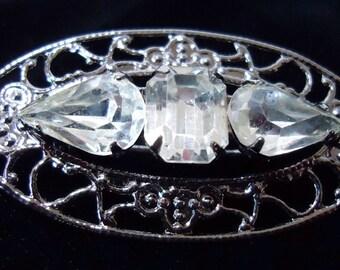Open work  oval shaped brooch,tear drop and rectangular stones set in a 'gun metal'.  Open work setting. FPAVI12.3-15.3.